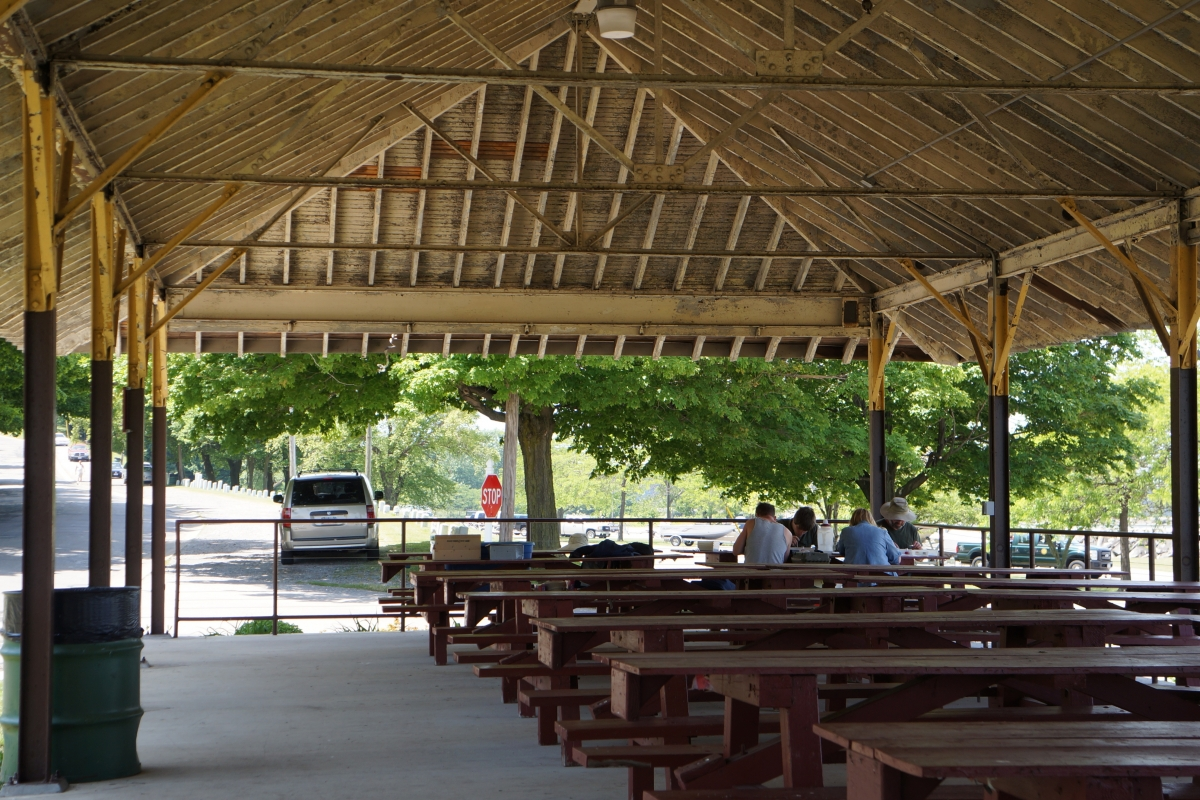 A group of people sitting at a table under a picnic structure