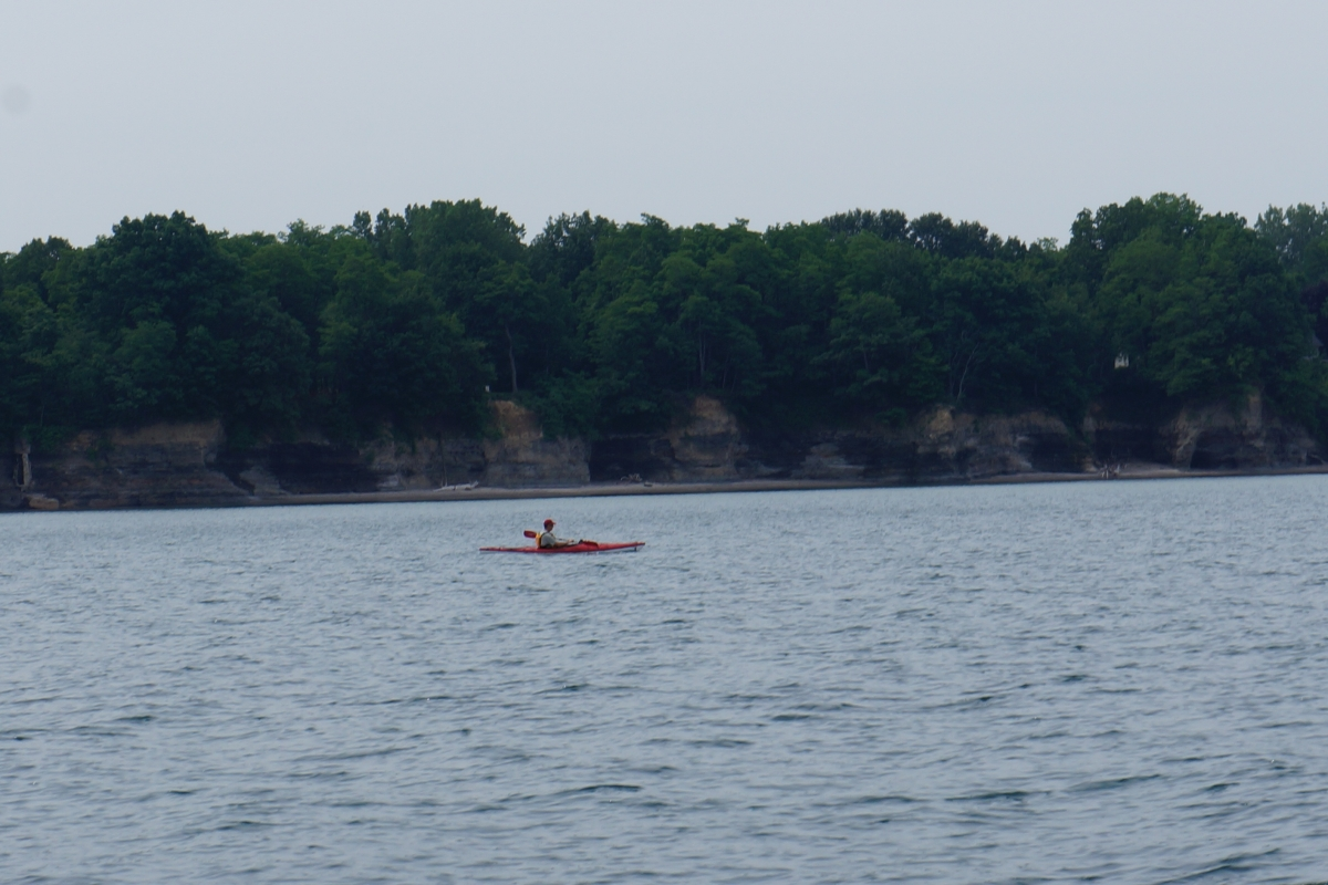 A person in a kayak paddles in front of a short cliff that is unevenly eroded
