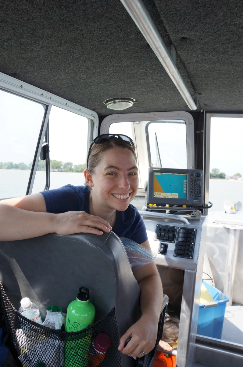 A person smiles, looking over the back of a seat inside the cabin of a boat. There is a screen with a map behind them.