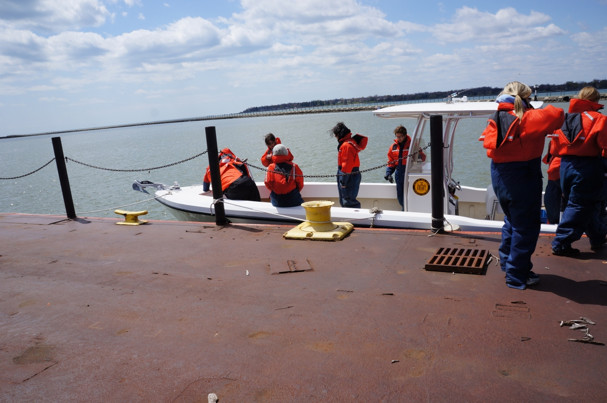 People in flotation suits step on board a fiberglass boat tied up at dock