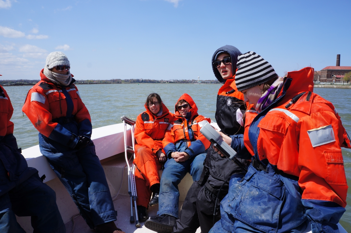 Students sitting in the front of the boat. One holds a sampling instrument. One of the students has crutches.