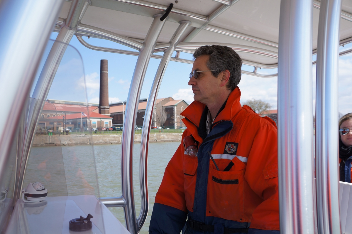 A person stands at the controls of the boat