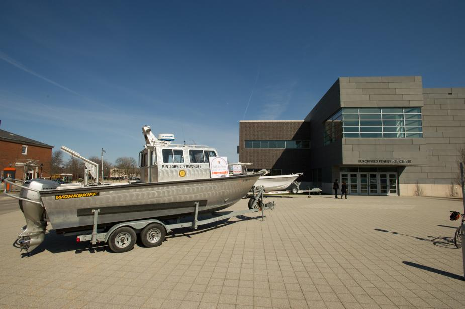 a silver boat sits on a trailer in front of a building with a placard for the 50th anniversary of the Great Lakes Center. There is the front of a white boat behind the first boat.