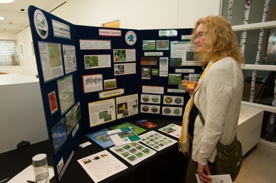 A person stands in front of a display board that has information about invasive species.