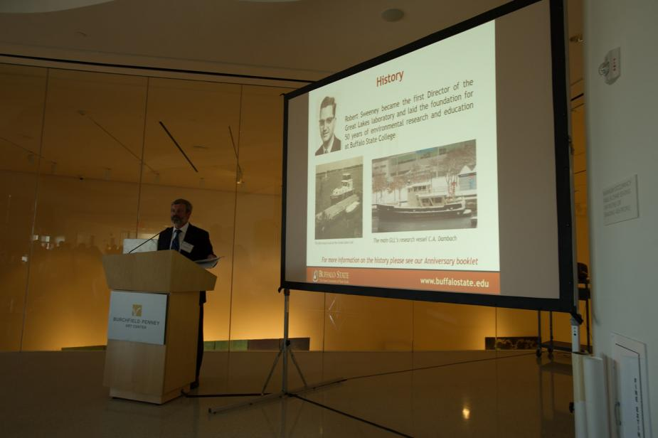a person stands at a podium to the left of a screen. There are some pictures on the screen and the word History at the top of the slide