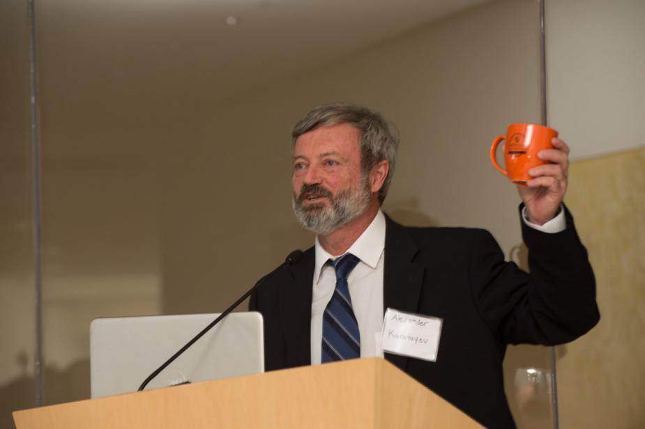 a person at a podium holds up a bright orange mug