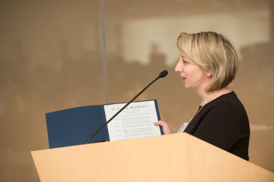 A person at a podium holds up a blue folder with a white paper inside