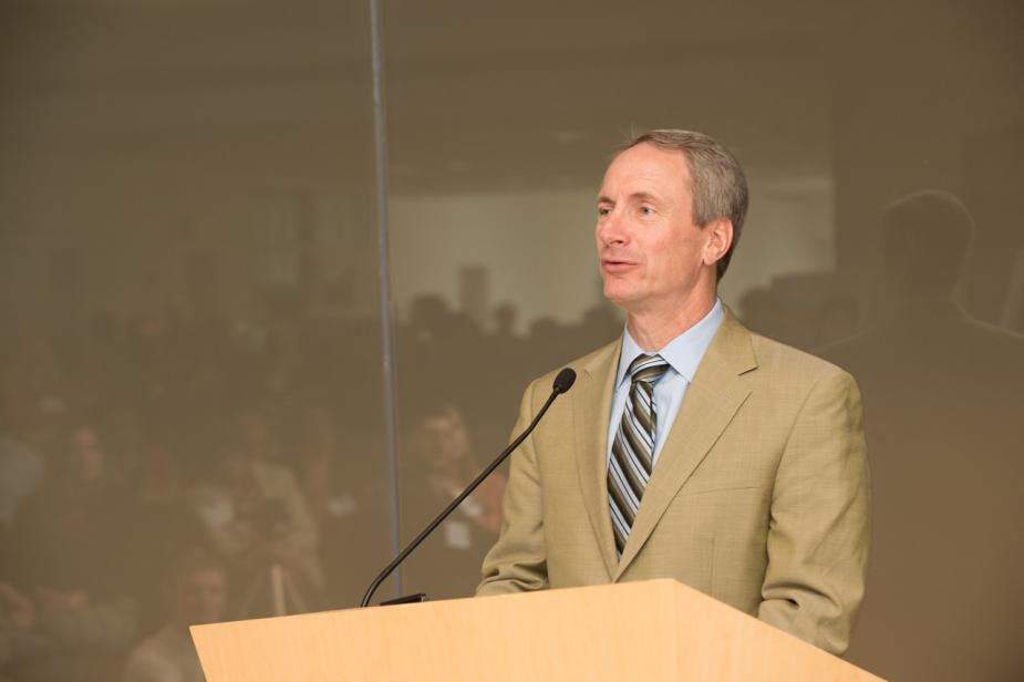 a person in a tan suit talking at a podium