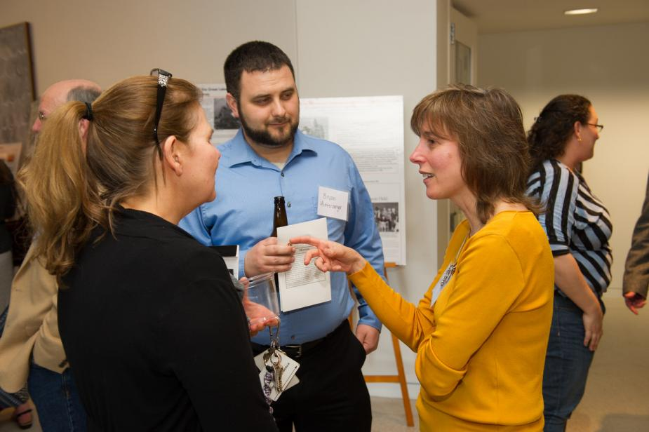 three people talk while other guests mingle in the background. The person in the middle has a name tag that says