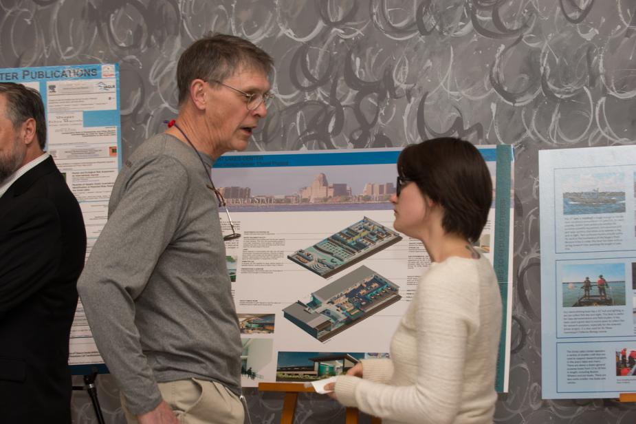 A person talks with a younger person in front of a poster on an easel