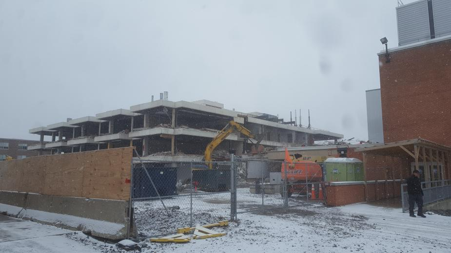 A construction site, where an excavator with a grapple is demolishing part of the building. The walls have been removed from this three-storey academic building. Fences surround the site, and there is snow on the ground.