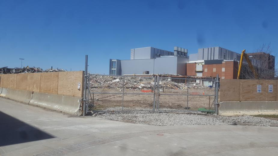 A field of debris next to a grey building and a brick building. The construction area is surrounded by a wooden fence that is interrupted by a chain-link fence through which we can see the debris.