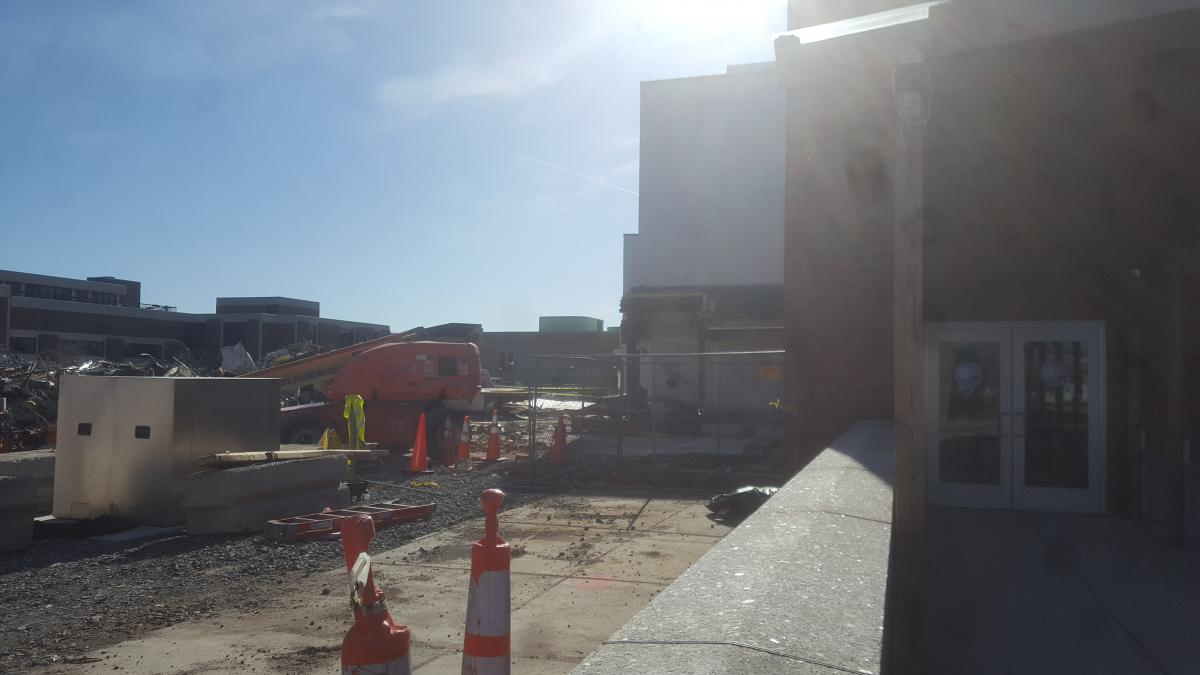 The same view as the previous picture, but the building part is gone. There is a cherry-picker where the building was, and some new equipment is in the foreground.