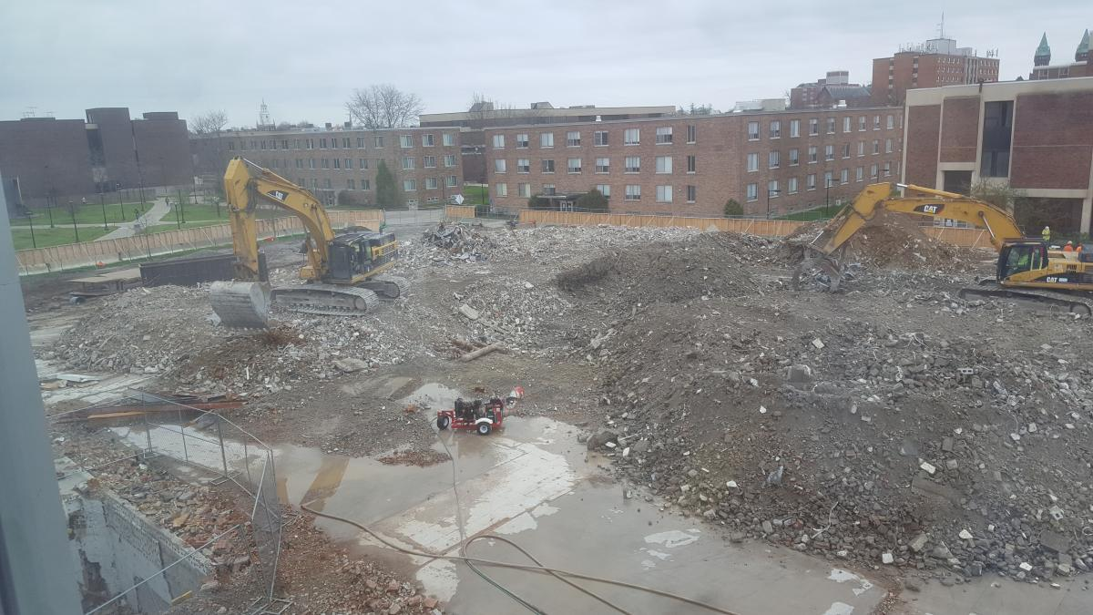 A field of rubble in a construction site, but there is some ground showing around the piles of rubble. Two excavators work to move and sort rubble. There is a generator on the clear ground.