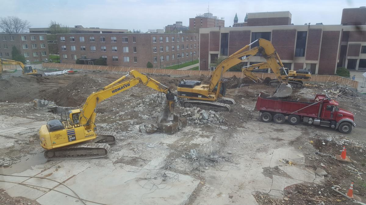 A construction site. One excavator is loading rubble into a dump truck. Another is using a jack hammer arm to break apart huge pieces of concrete. Two other excavators dig in the background.