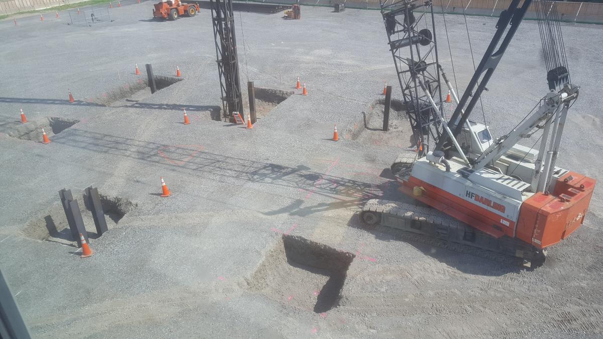 A crane pounding steel beams into sqaure holes in the ground. There are six holes and each have multiple beams driven into them.
