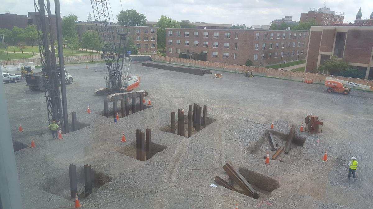 A crane pounding steel beams into sqaure holes in the ground. There are eight holes and each have multiple beams driven into them.