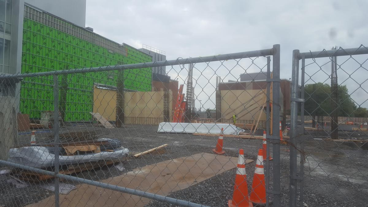 A construction site through a chain-link fence. The siding has been pulled off an existing building and the forms of new walls and rebar columns rise out of the ground next to it.