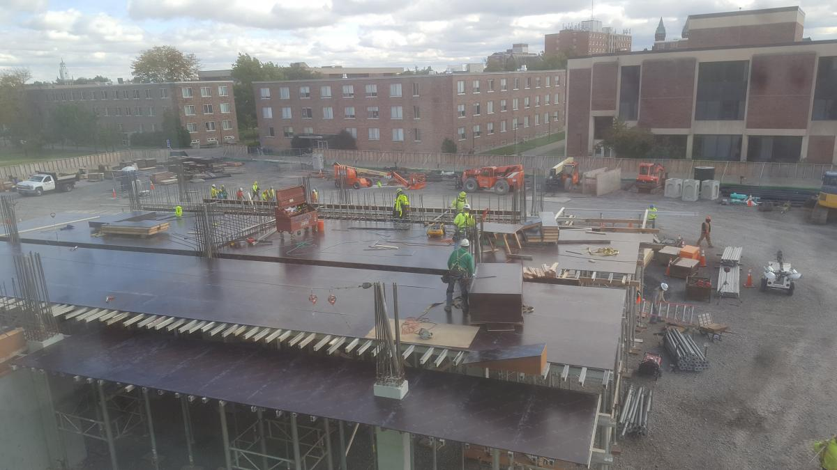 Construction workers stand on steel plates placed across the first floor of a building under construction.