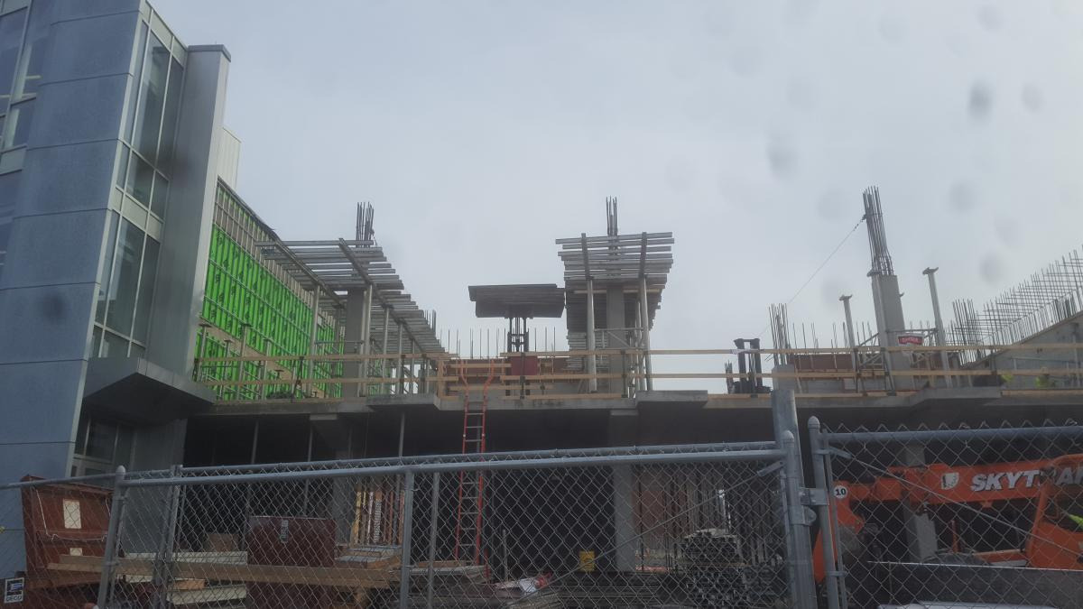 A building under construction. Struts are being put up on the second floor.