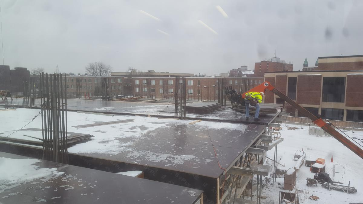 A construction worker supervises as a fork lift places steel plates on the second floor of a building under construction. There is snow on the steel plates that comprise the floor.