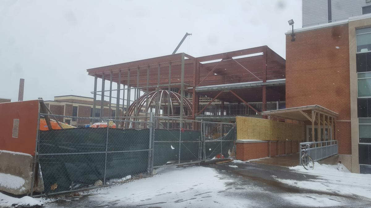A building under construction with a large steel frame surrounding a dome made of steel beams. There is snow on the ground.