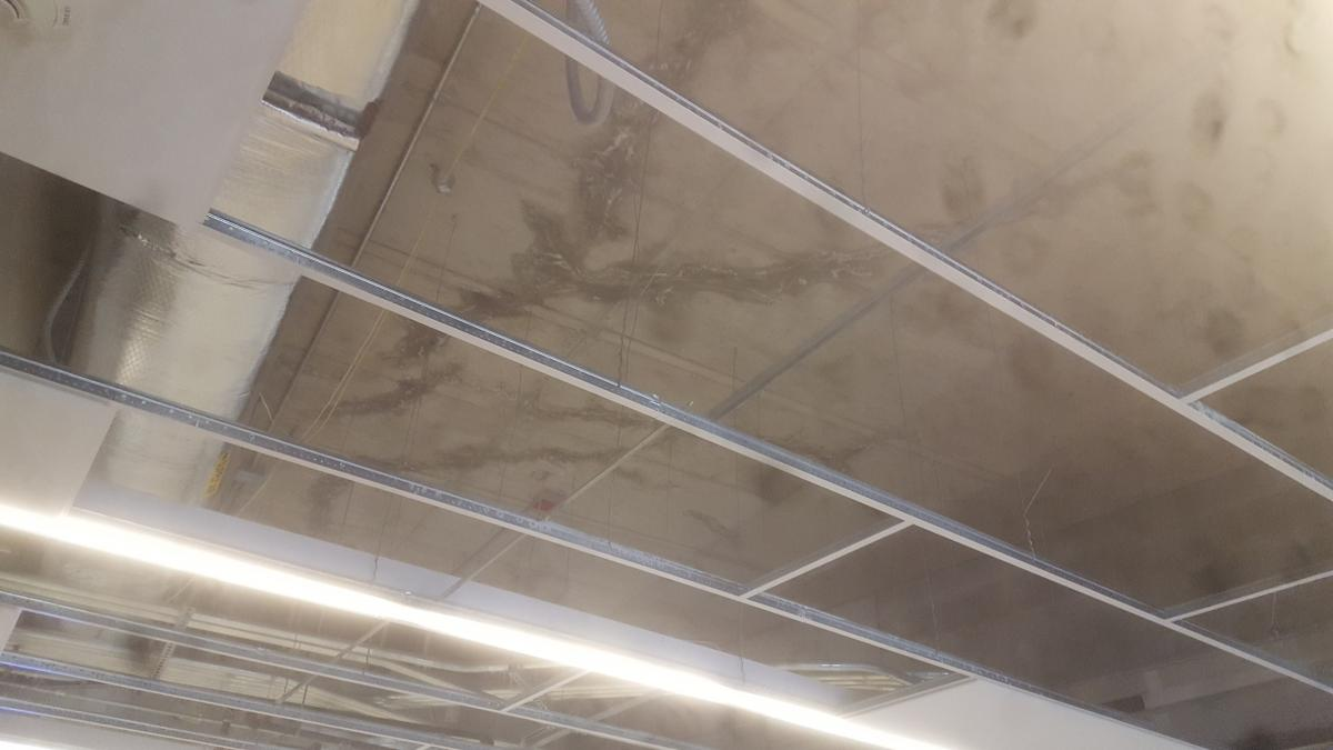 A concrete ceiling with cracks or staining.