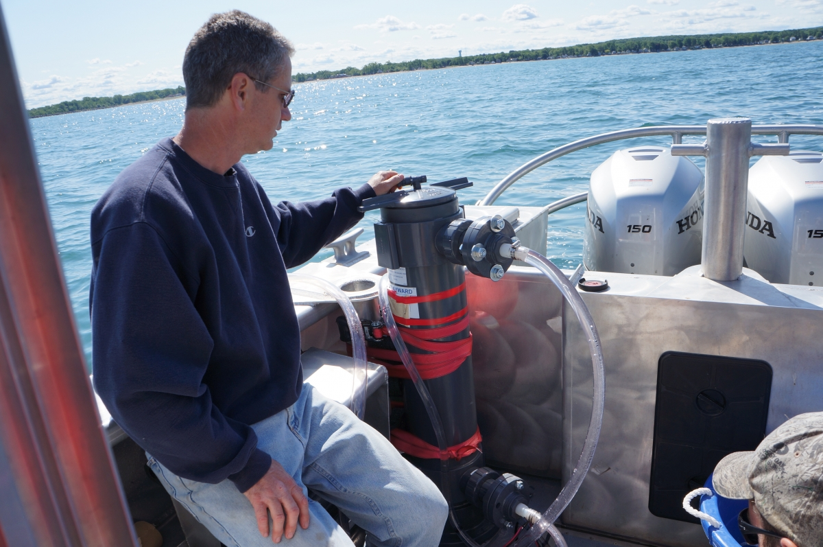A person sits on a boat next to a PVC cylinder with tubes running out of it