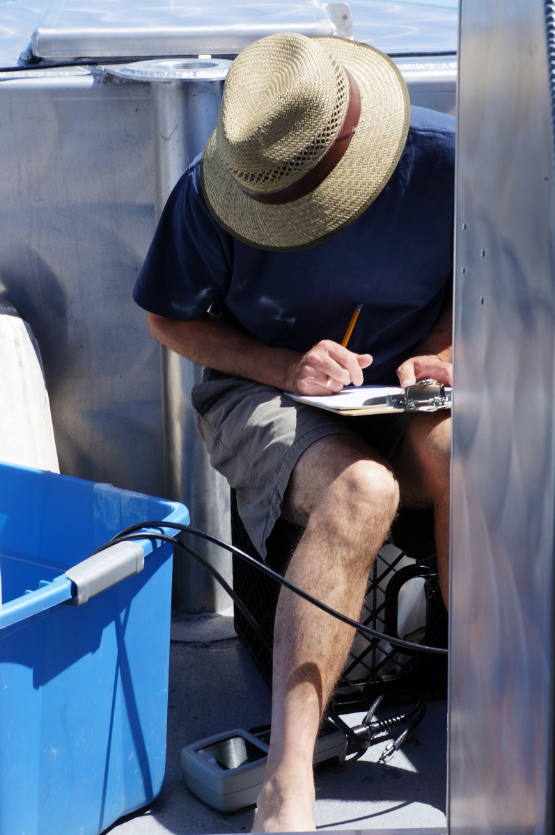 A person with a hat obscuring their face works on a boat. They are sitting on a milk crate, looking down at an instrument on the floor, and writing something on a clipboard.