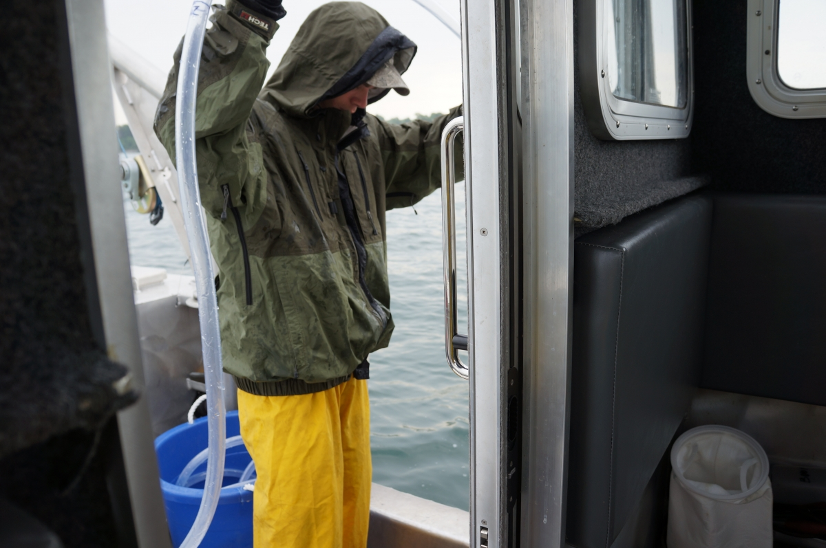 A person in rain gear stands on a boat and holds a tube over their head