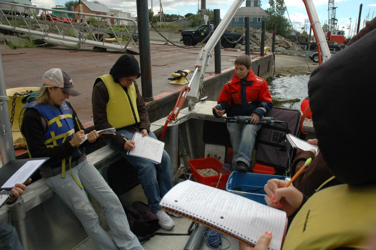Students sit on a boat tied up at dock while a person in a floatation coat holds up a research instrument