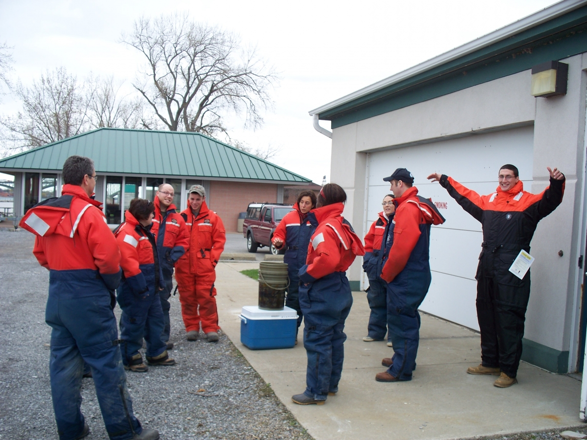 A group of people standing by a garage door wearing flotation suits. There is a cooler and some buckets.