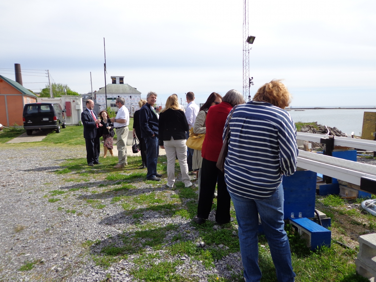 People stand outside looking at troughs set up near the waterfront.