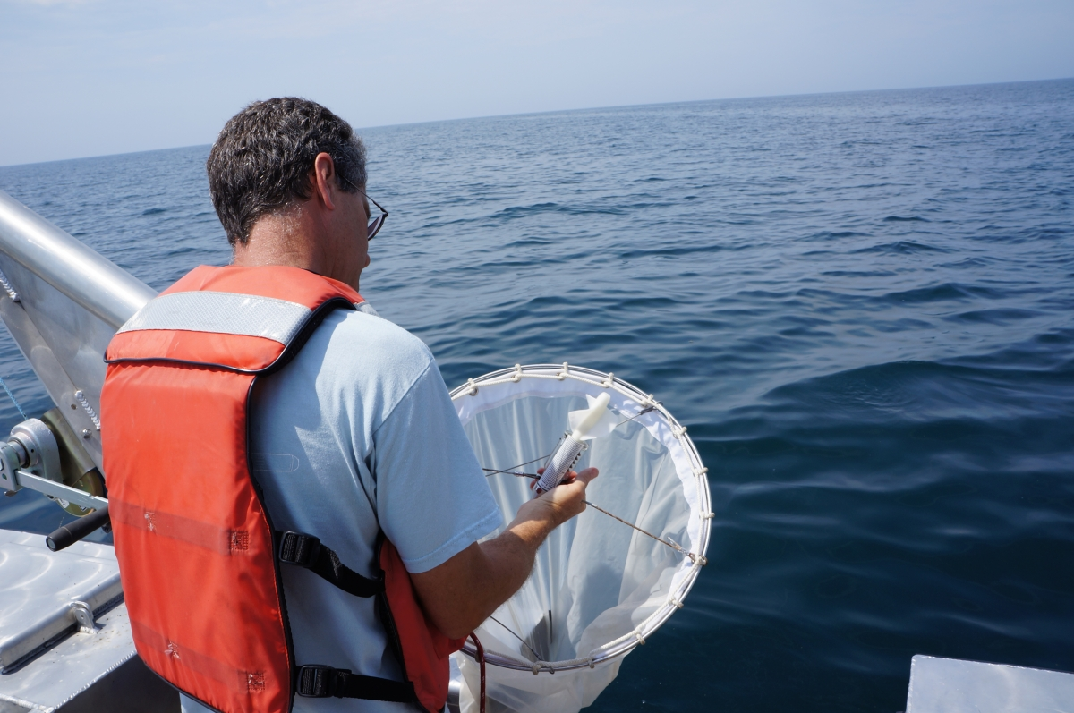 A person in a life jacket on a boat holds up a round net and looks at a device in the mouth of the net