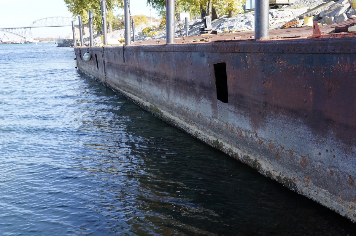 A barge that is used as a dock. The high water level is visible at least a foot above the water, and the water is below the bottom of the barge by a few inches.