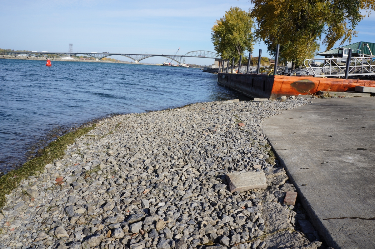 A stretch of gravel leading down to the water. There is a concrete pad further up the slope from the gravel