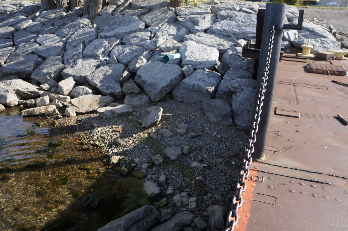 The area next to the dock has a neatly arranged stone shoreline, and gravel with some shallow water.