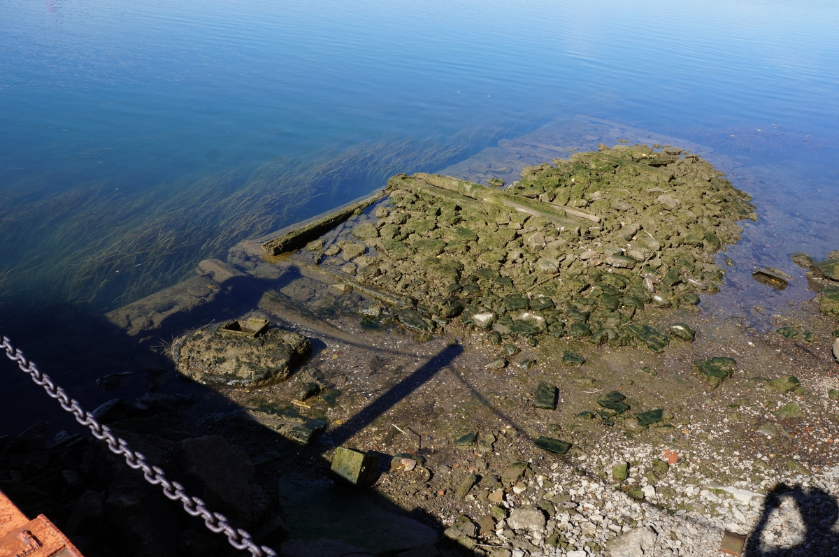 almost the entire shape of algae-covered stone and wood cribbing is visible above the water.