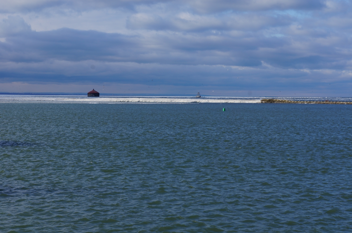 Ice coats the break wall, but the water nearby is clear of ice. There is a roundhouse in the water on the other side of the ice.