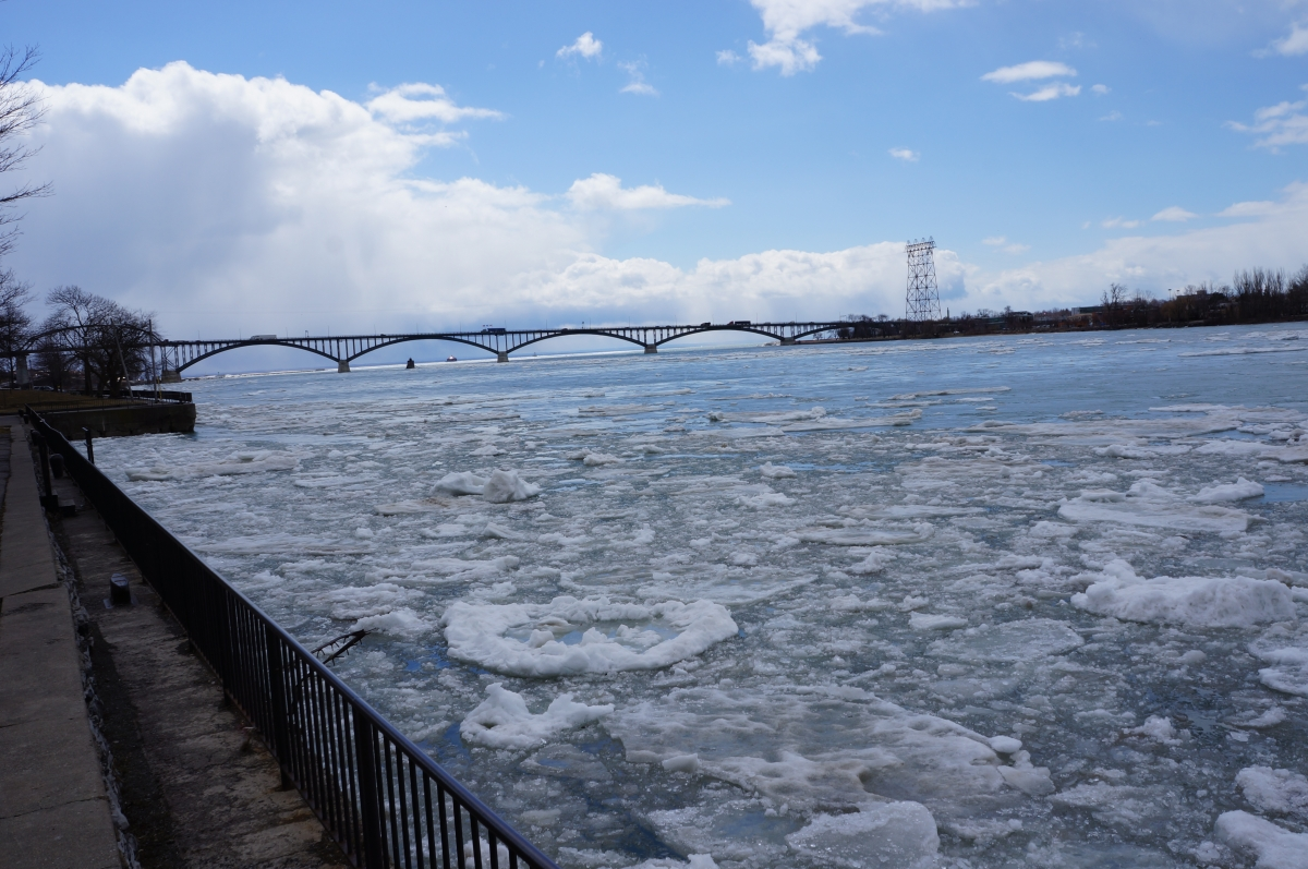 Ice chokes the river near the break wall. There is a bridge in the distance.