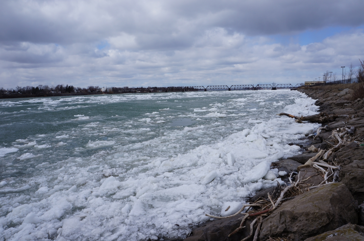 Ice piling up along the shore of the river. There is a bridge in the distance.