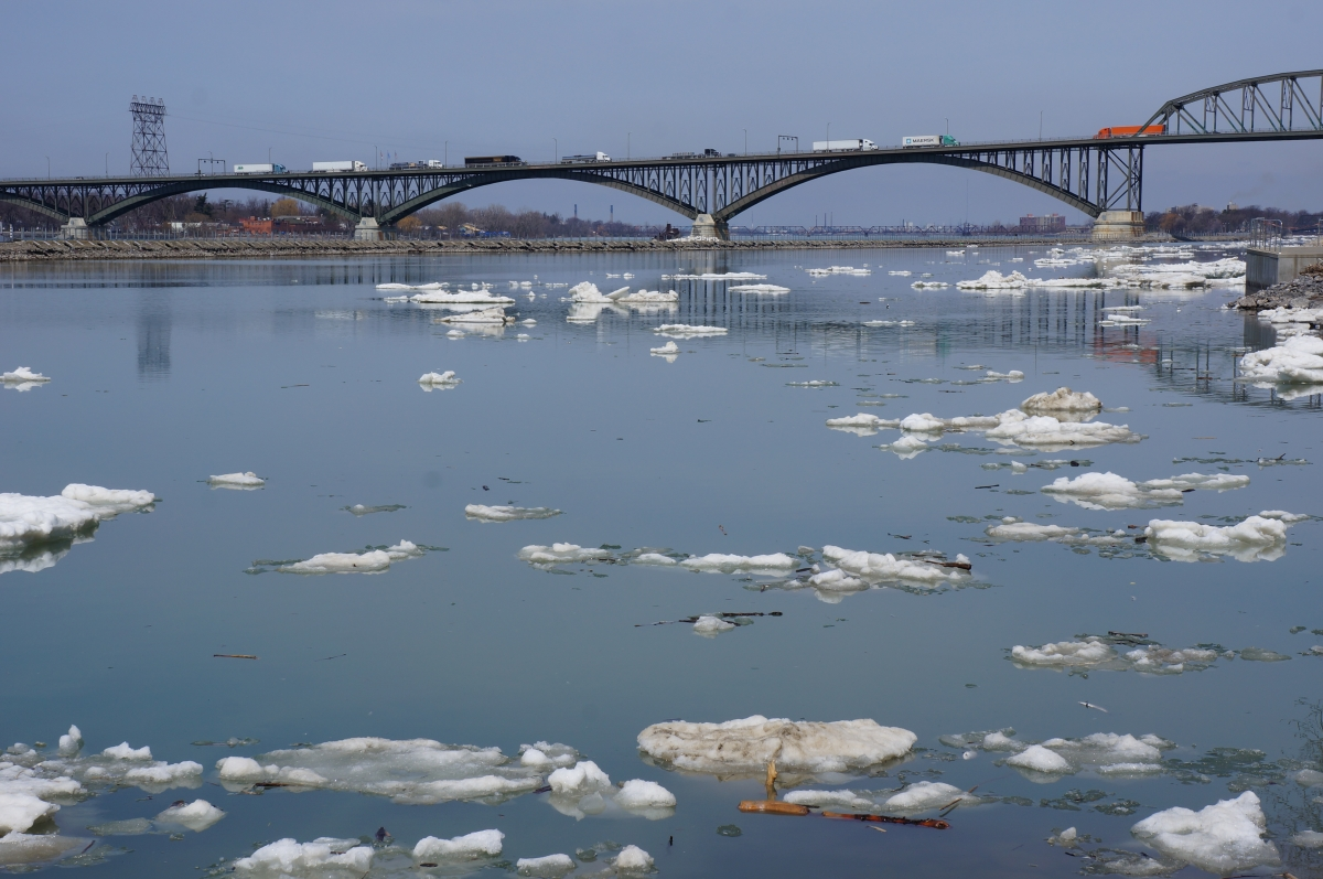 A few pieces of ice in the water. There is a breakwall and a bridge in the distance.