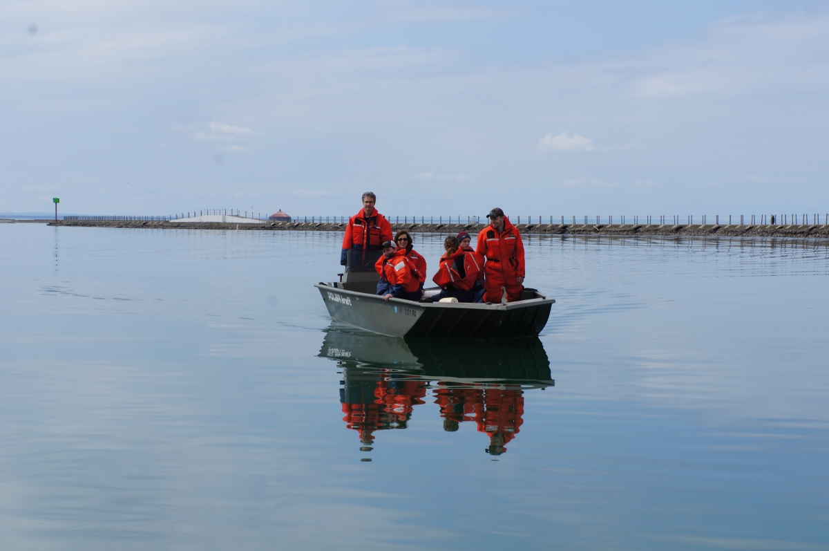 A group of people in flotation suits aboard a shallow boat on glass-calm water