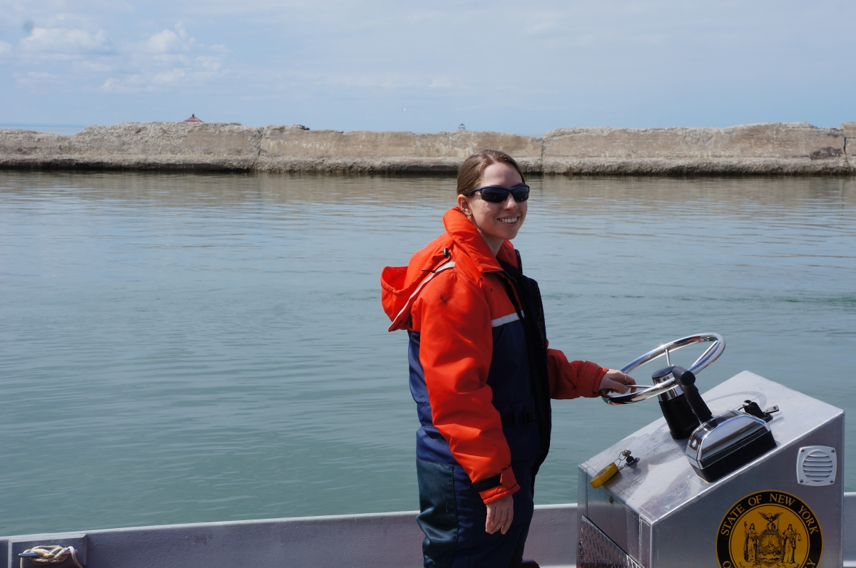 A person standing up at the helm of a boat. A breakwall is the the background