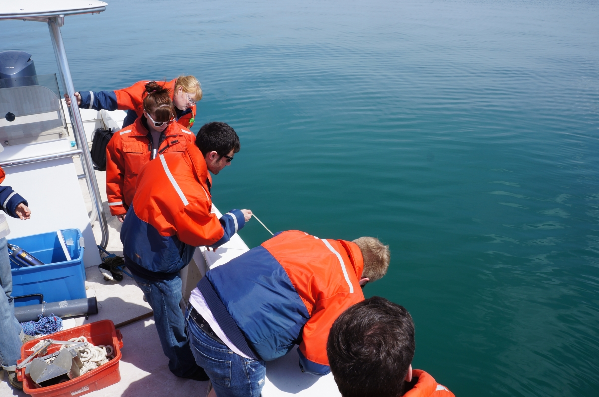 People in flotation coats lean over the side of a boat to watch one of them deploy some equipment