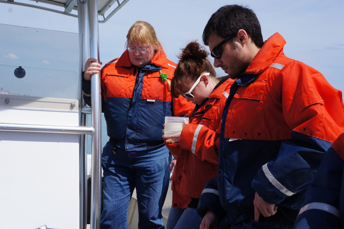 People in flotation coats stand on a boat. One looks at water in a clear plastic jar