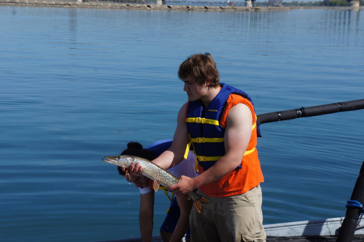 A person stands in front of water holding up a large brown fish with lighter speckles