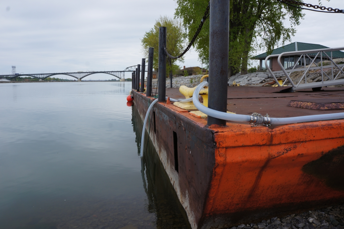 A hose is drapped over a metal dock and into the water.