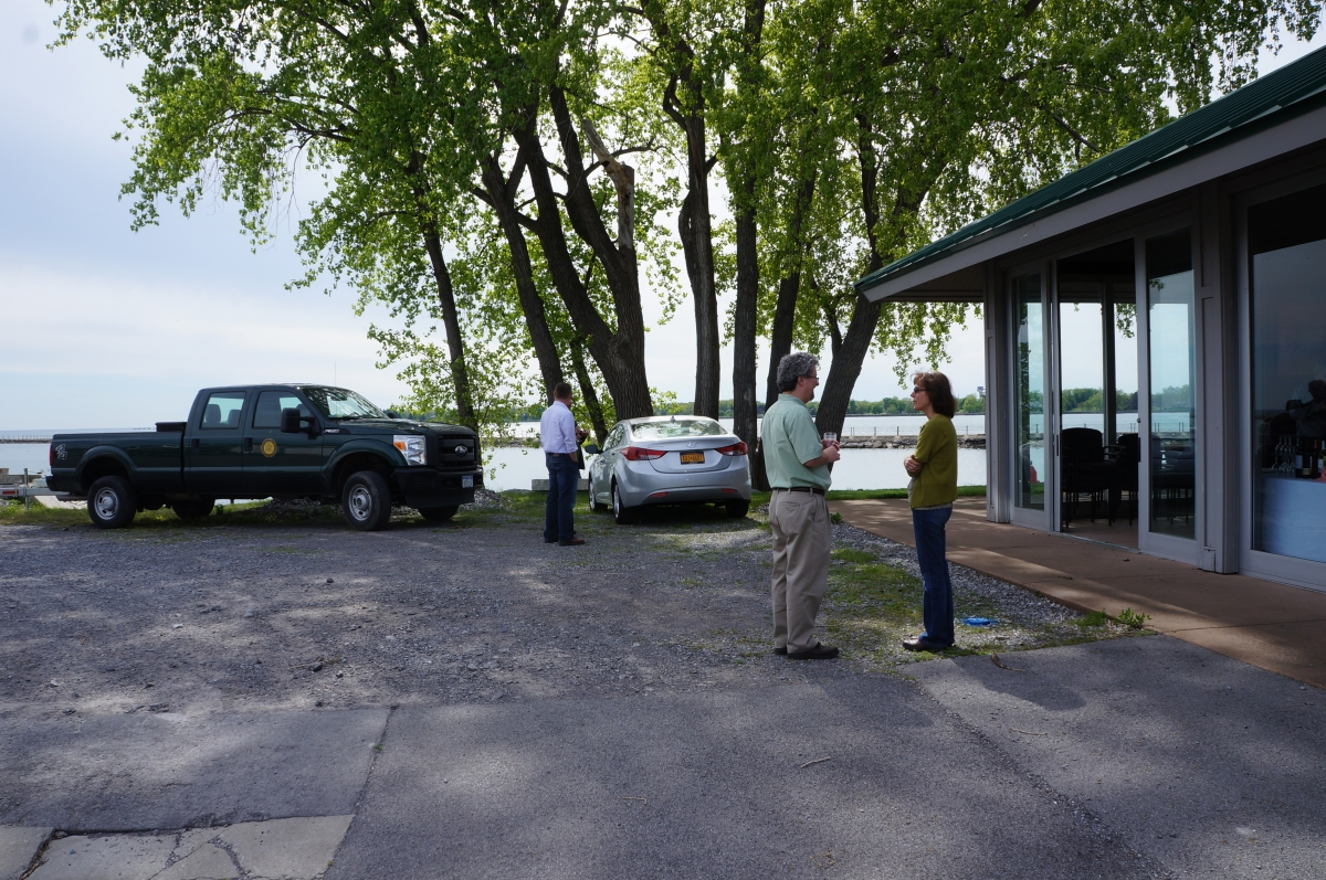 People stand by some vehicles near a pavilion building. Behind them is a tall tree and a waterway.