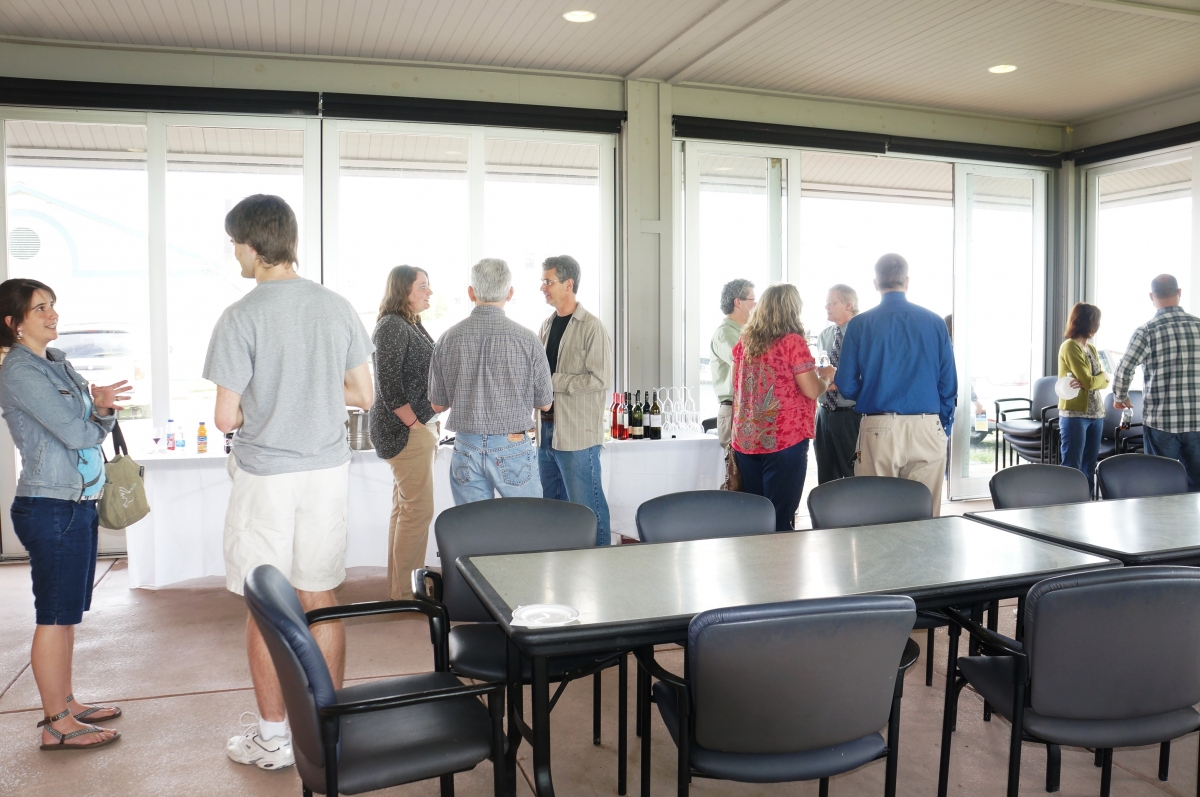 People mingling by the refreshments set up by the glass walls of a pavilion.